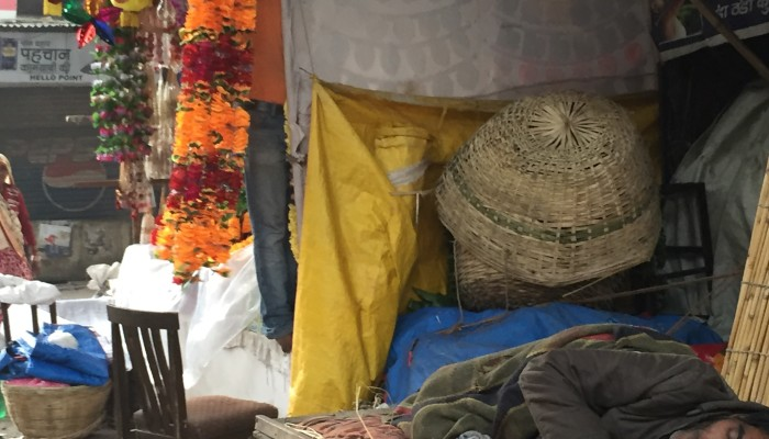 Coconut water vendor asleep in Indian market.